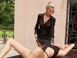 Domineering Sandra Hill has her submissive Bianca well in hand as she leads her by a red leash to a massage table, where she binds the hapless girl.